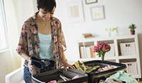 gettyimages519515569_young_woman_packing_suitcase_200x118
