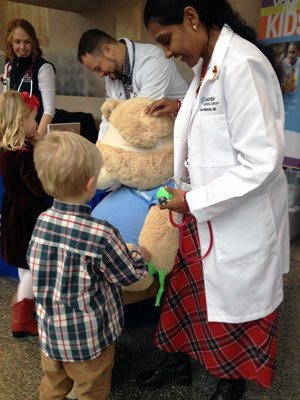 Now that he knows Mr. Bear's heart is strong, this little doctor moves on to fixing the patient's broken leg with neon-green bandage tape.