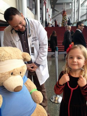 Swedish Medical Center sports medicine specialist Terrence Cronin, M.D., looks on as another junior doctor successfully applies a head bandage to Mr. Bear and prepares to auscultate his heart.