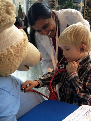 A child offers a second opinion on Mr. Bear's cardiac status while Uma Pisharody, M.D., a Seattle pediatric gastroenterologist with Swedish Medical Group, looks on with a smile.