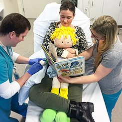 Demonstration: Comforting a child during a medical procedure - child's back to a caregiver's stomach/chest.