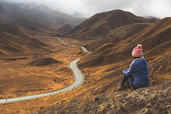 gettyimages813441886_woman_sitting_on_mountain_side_350