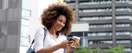Girl looking at mobile phone while walking downtown